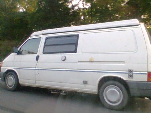 White T4 camper van barreling down the road.
