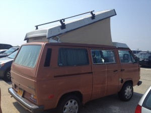 orange t3 van with pop top in a beach parking lot