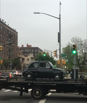 Black original Fiat 500 on flatbed truck