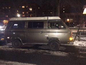 Brown T3 van parked on street at night, glare