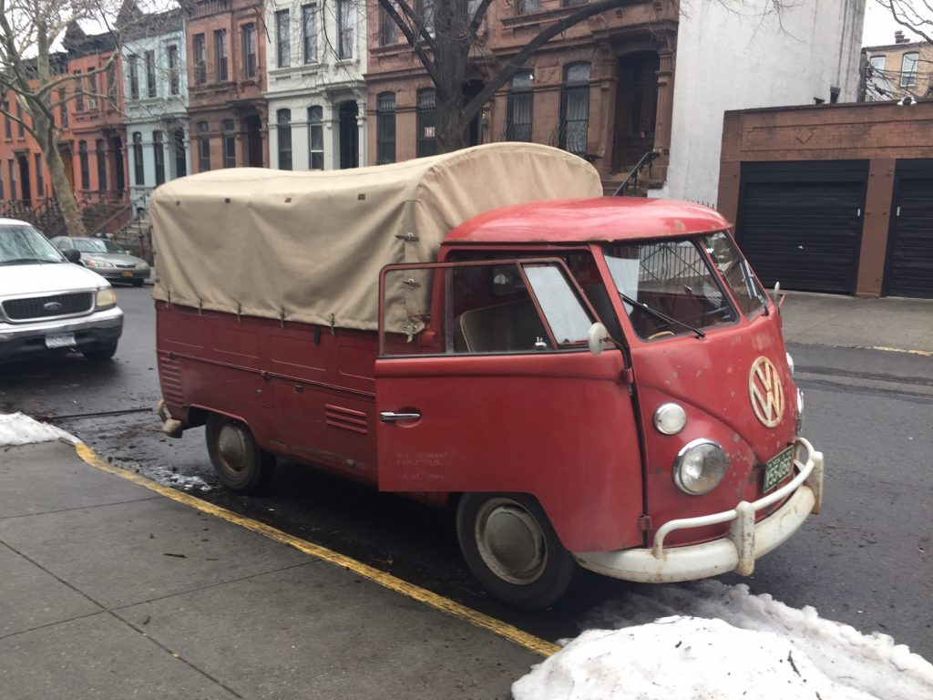 Red t1 utility van with canvas bed cover parked on street