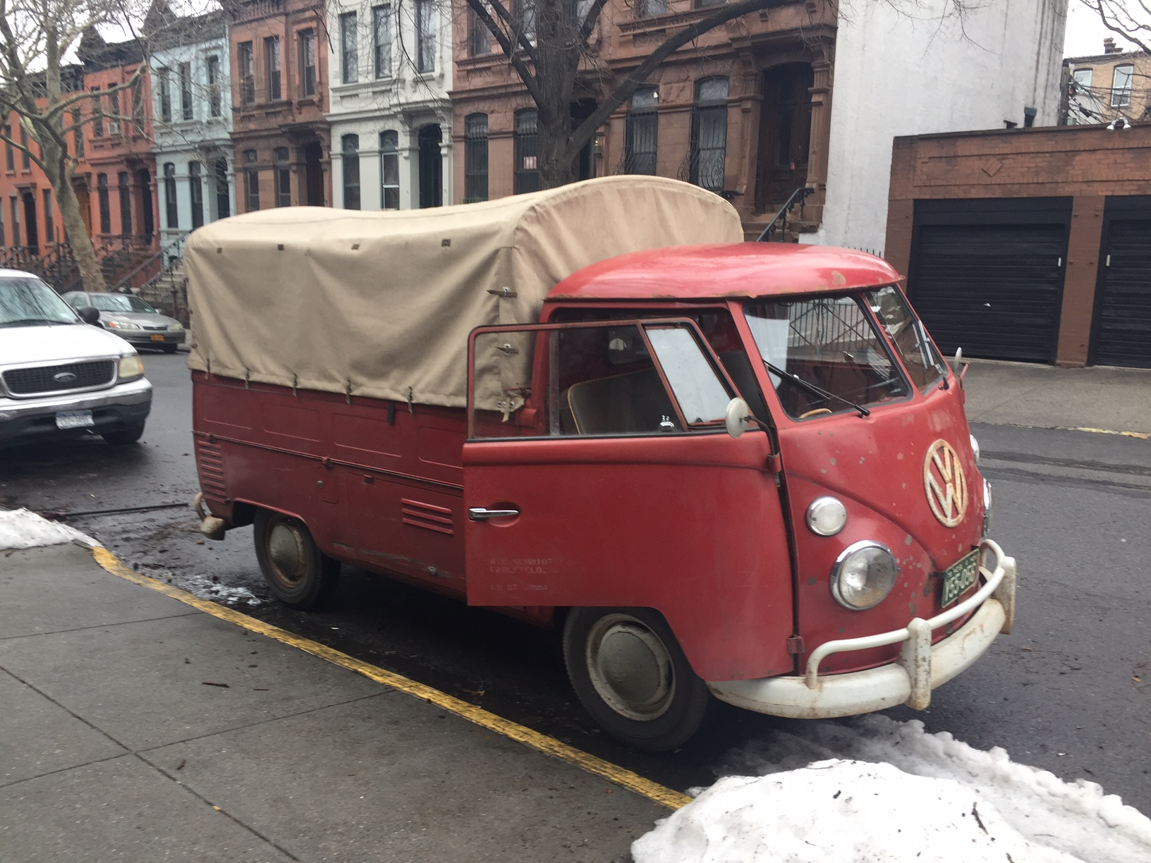 a93773fed0 Red t1 utility van with canvas bed cover parked on street