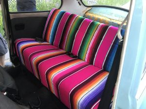 rear seat of vw beetle covered in mexican blankets