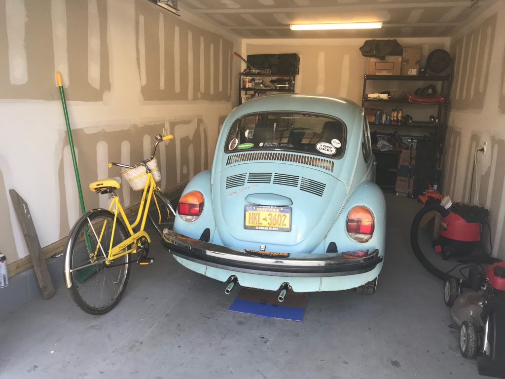 Blue beetle parked in garage next to yellow bicycle
